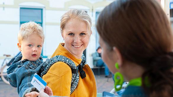 vrouw met baby op de rug ontvangt een kaartje